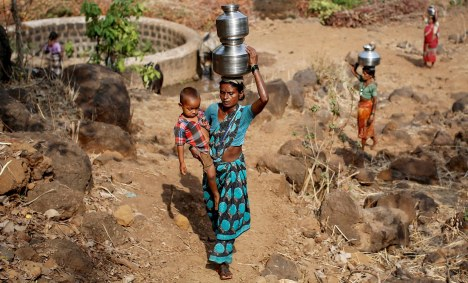 "Shivarti, the second wife of Namdeo, holds her grandson while carrying metal pitchers filled with water from a well outside Denganmal village, Maharashtra, India, April 21, 2015. In Denganmal, a village in Maharashtra state, some men take a second or third wife just to make sure their households have enough drinking water. Becoming what are known as ""water wives"" allows the women, often widows or single mothers, to regain respect in conservative rural India by carrying water from the well quite some distance from the remote village. When the water wife, who does not usually share the marital bed, becomes too old to continue, the husband sometimes takes a third and younger spouse to fetch the water in metal pitchers or makeshift containers. REUTERS/Danish Siddiqui TPX IMAGES OF THE DAY PICTURE 22 OF 29 FOR WIDER IMAGE STORY ""WATER WIVES OF MAHARASHTRA""